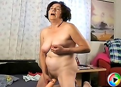 Granny plays with her tits and nails her old cunt with a dildo